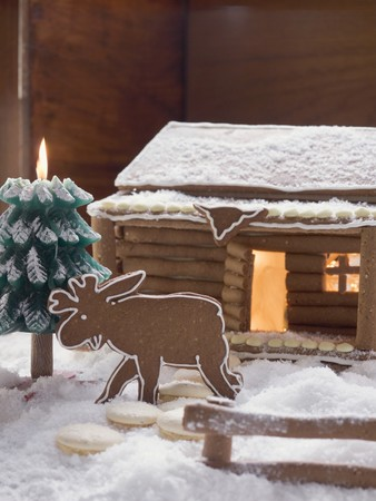 figurative: Gingerbread log cabin in snowy forest with gingerbread elk