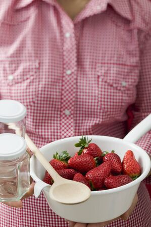 fragaria: Woman holding strainer full of strawberries, jam jars, spoon