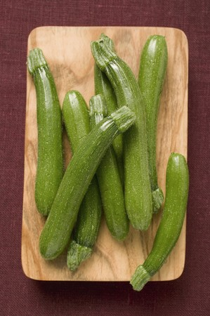 cocozelle: Several courgettes on chopping board LANG_EVOIMAGES