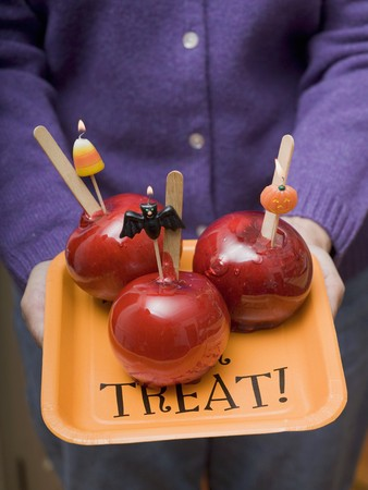 ignited: Woman holding tray of toffee apples for Halloween