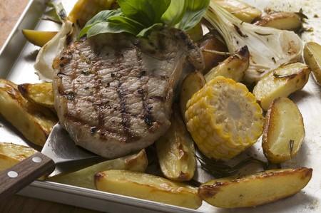 grilled pork chop: Grilled pork chop on roasted vegetables LANG_EVOIMAGES