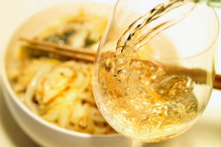 no movement: Pouring a glass of wine, noodle dish in background