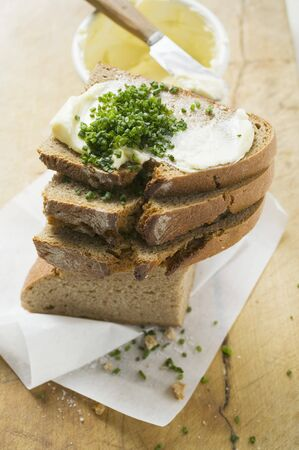 several breads: Several slices of bread in a pile with butter and chives