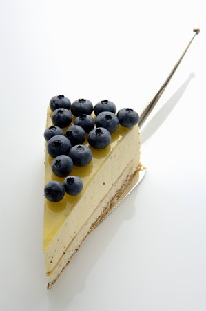 cream cake: A piece of lemon cream cake with blueberries LANG_EVOIMAGES