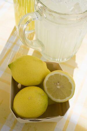 soda pops: A jug of lemonade and fresh lemons
