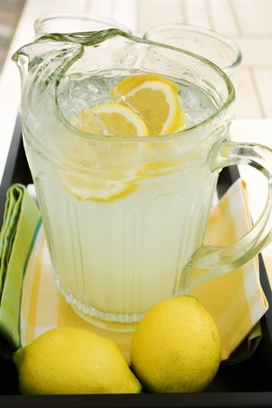 Lemonade in a glass jug with slices of lemon and ice LANG_EVOIMAGES