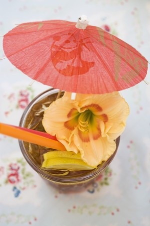 bacardi: Cuba Libre with cocktail umbrella and amaryllis flower LANG_EVOIMAGES