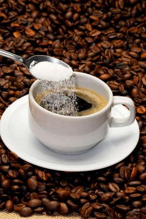 sprinkling: Sprinkling sugar into coffee LANG_EVOIMAGES