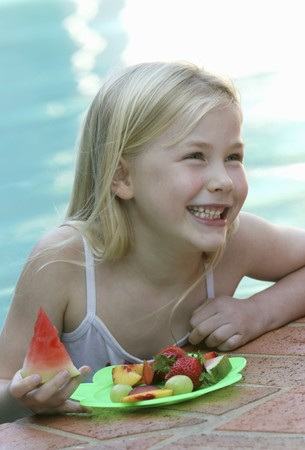well beings: Small girl with fresh fruit at the pool LANG_EVOIMAGES