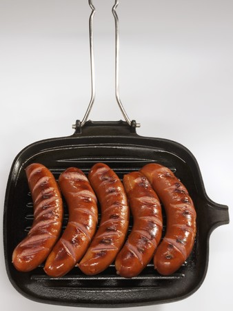 scalded sausage: Five bockwurst sausages in a grill pan