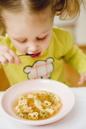 noodle soup: Small girl eating teddy bear noodle soup LANG_EVOIMAGES