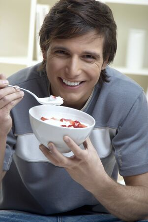 well beings: Young man eating quark with fresh strawberries LANG_EVOIMAGES
