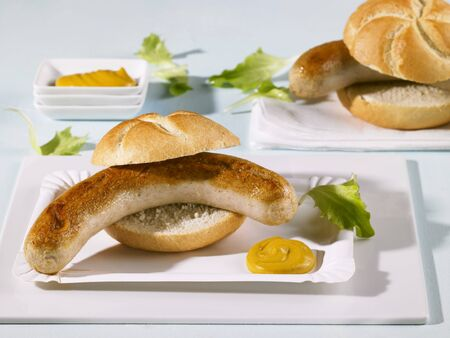 paper plates: Two bread rolls filled with sausages on paper plates LANG_EVOIMAGES