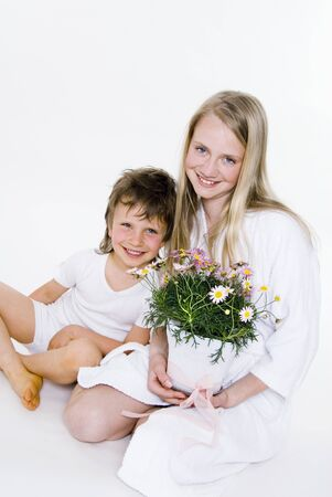 13 15 years: Girl holding pot of marguerites, boy sitting beside her