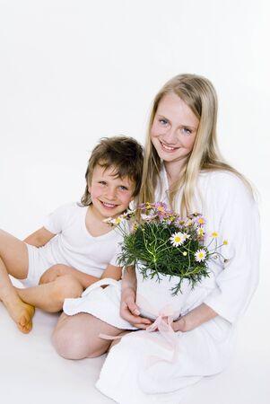 marguerites: Girl holding pot of marguerites, boy sitting beside her