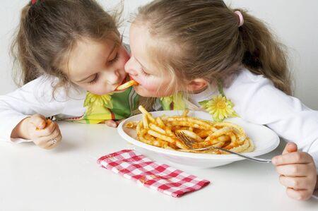 5 10 year old girl: Two girls eating macaroni with tomato sauce