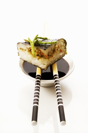 substantial: Sushi on chopsticks on a small bowl of soy sauce LANG_EVOIMAGES