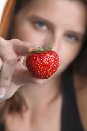 30 to 35 year olds: Young woman holding a strawberry