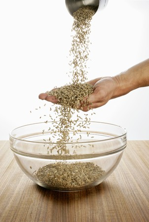 secale: Someone pouring rye over their hand into a glass bowl