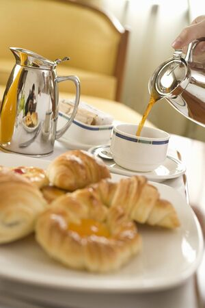 coffeepots: Pouring a cup of coffee with pastries in foreground