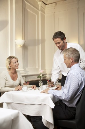 35 to 40 year olds: Waiter serving a mature married couple in a restaurant