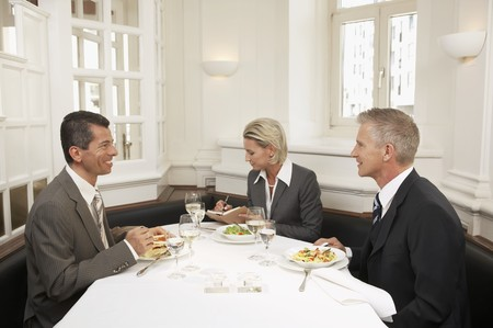 conviviality: Woman between two men at a business meal