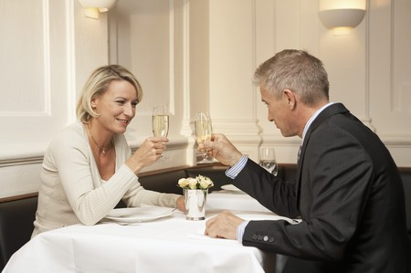 35 to 40 year olds: Married couple raising glasses of sparkling wine