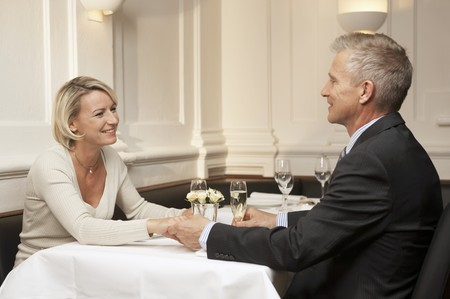 hold ups: Married couple sitting at restaurant table holding hands