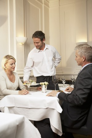 35 to 40 year olds: Waiter serving the main course in a restaurant