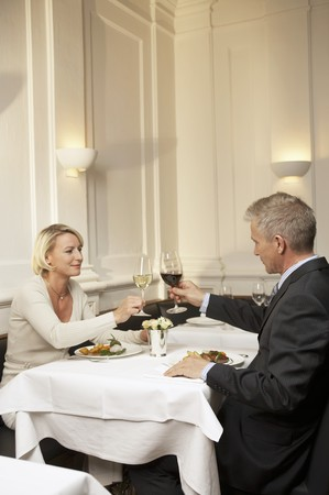 35 to 40 year olds: Married couple raising glasses of wine during a meal LANG_EVOIMAGES