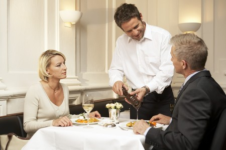 35 to 40 year olds: Waiter seasoning a mans food in a restaurant