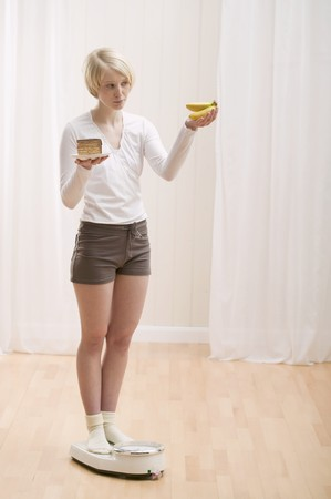 well beings: Young woman with a piece of cake and bananas on scales
