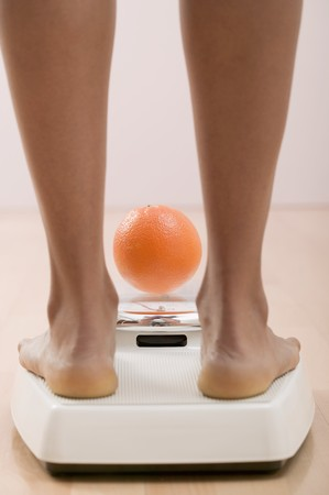 well beings: Young woman on bathroom scales with orange