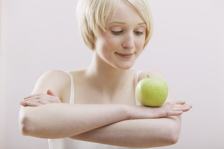 well beings: Young woman balancing an apple on folded arms