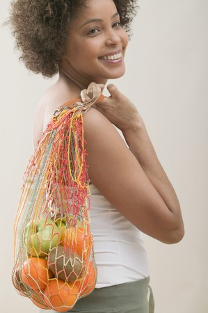 well beings: Young woman with a string bag full of fruit