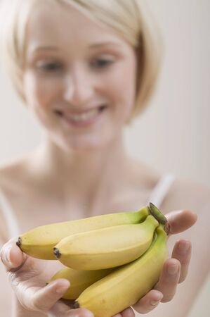 20 to 25 year olds: Young woman holding bananas