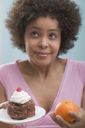 enquiring: Young woman undecided between cake and orange