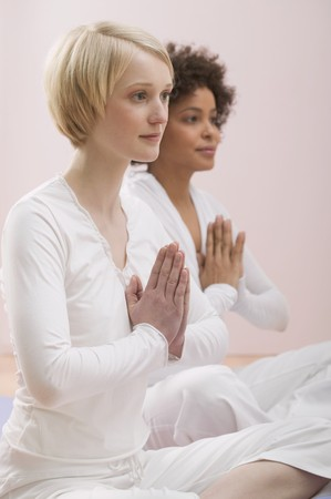25 to 30 year olds: Two young women meditating LANG_EVOIMAGES
