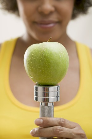 hand weight: Young woman balancing a fresh apple on a hand weight LANG_EVOIMAGES