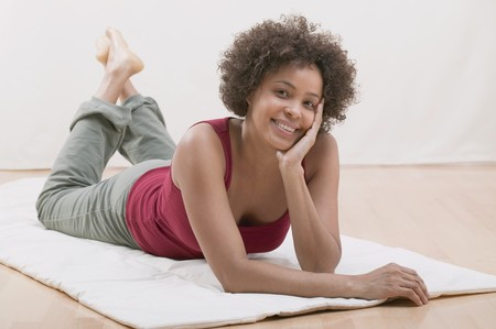 20 to 25 year olds: Cheerful young woman lying on a mat (relaxed)