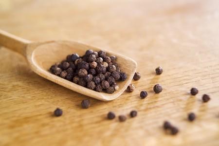 wooden scoop: Black peppercorns on a wooden scoop