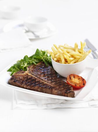 qs: T-bone steak with chips and grilled tomatoes LANG_EVOIMAGES