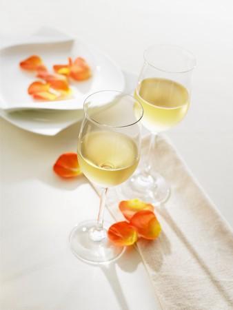 花びら: 花びらで飾られたテーブルの上の白ワインを 2 杯 LANG_EVOIMAGES
