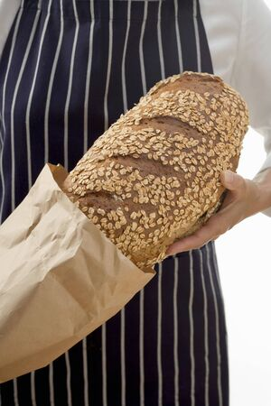 soft sell: Woman putting a loaf of oat bread into a paper bag LANG_EVOIMAGES