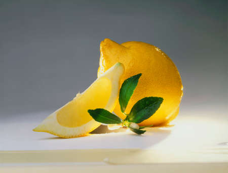 lemon wedge: Whole lemon and lemon wedge, lemon leaves LANG_EVOIMAGES