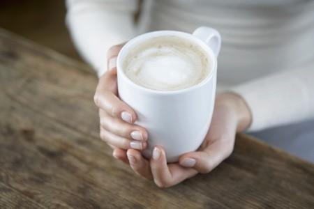 cappuccio: A pair of hands holding a cappuccio cup