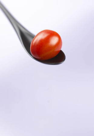 plastic spoon: Red cocktail tomato on a black plastic spoon