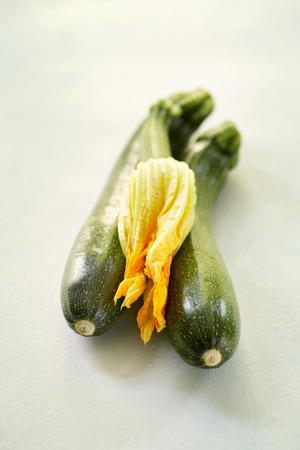 Two courgettes and a courgette flower LANG_EVOIMAGES