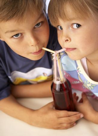 soda pops: Children drinking fizzy drink through straws LANG_EVOIMAGES