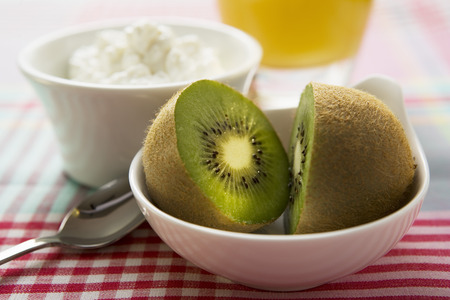 body consciousness: Halved kiwi fruit in front of a small bowl of cottage cheese LANG_EVOIMAGES